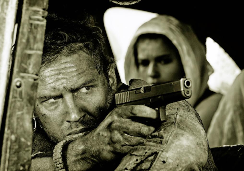 Том Харди целится из пистолета