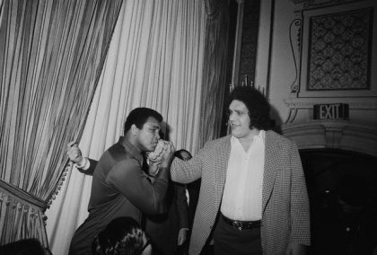 """25 Mar 1976, New York, New York, USA --- Ali Meets a Giant. New York: When World Heavyweight Boxing Champion Muahmmad Ali was in New York, March 25th, 1976 to meet Japanese wrestler Antonio Inoki, whom he will meet in a boxer versus wrestler match in Tokyo, June 26th, someone caught his eye --- it was seven-foot-four Andre, the Giant, a wrestler from France and friend of Inoki. The towering Asdre became the object of Ali's attention after he was through trading barbs with Inoki. Ali, so taken in by the man who made him look diminutive by comparison, literally bowed to Andre and then matched his hand against Andre's massive palm. All later placed """"The Giant's"""" fist on his jaw -- glad he won't have to face such a blow. --- Image by © Bettmann/CORBIS"""