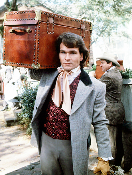 American actor Patrick Swayze (1952 - 2009) carrying a trunk, as Orry Main in the TV miniseries 'North And South', 1985. (Photo by Silver Screen Collection/Getty Images)